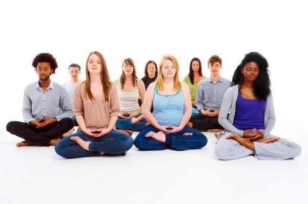 group of people sitting cross-legged in meditation poses