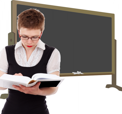 person with short hair in front of chalkboard looking at a book
