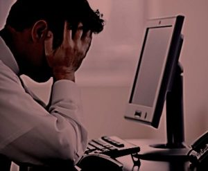 person sitting at computer with head in hands
