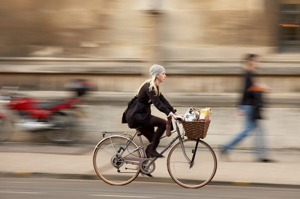 person riding cruiser bike with a basket on it. The person has shoulder length blonde hair and is wearinga black coat and grey woven hat. The person is riding on a street next to a sidewalk with blurry background images.