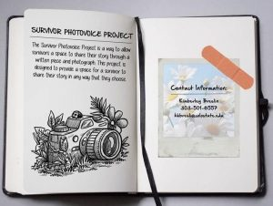An open notebook with a drawing of a camera and text