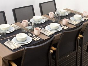 A table set for six with placemats, silverware, cups and dishes