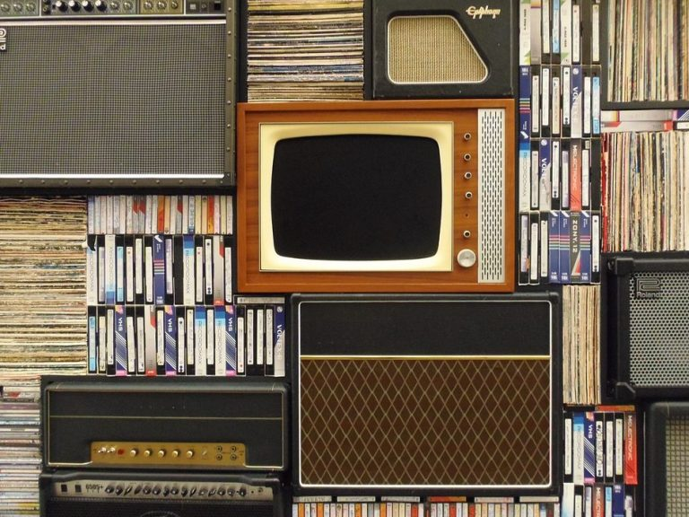 An old tv surronded by cassettes, speakers, and other things