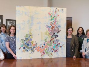 a group of people standing next to a piece of artwork