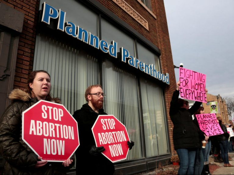 Anti-abortion activists (L) rally next to supporters of Planned Parenthood outside a Planned Parenthood clinic in Detroit, Michigan, U.S., February 11, 2017.