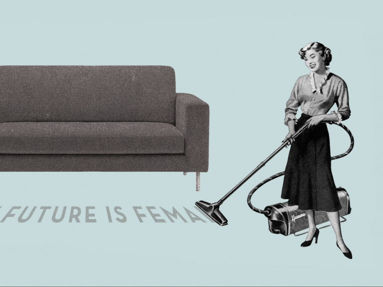 """A woman vacuums up dirt on the carpet that spells """"The Future is Female"""""""