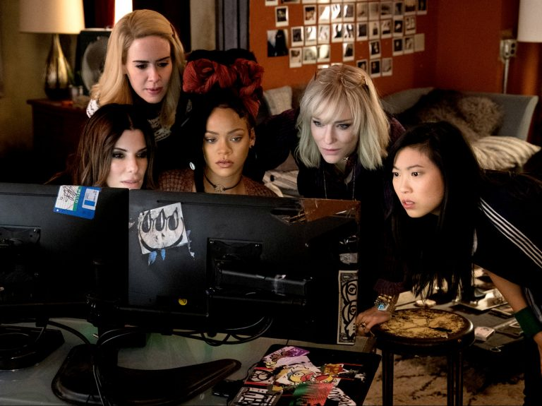Cast of Ocean's 8 gathered around a computer screen
