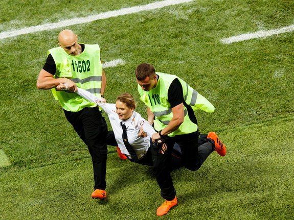 Member of Pussy Riot being dragged off the field at the World Cup