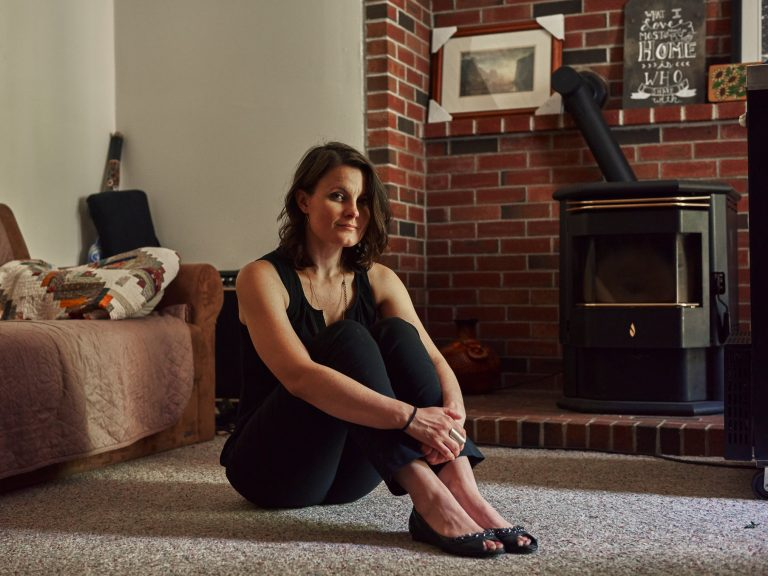 A woman sits on the floor or her apartment and looks at the camera