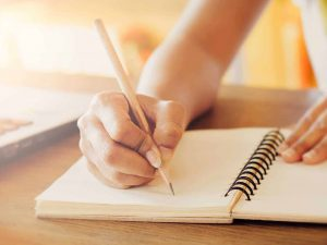 Close up image of a person writing in a blank notebook with a pencil