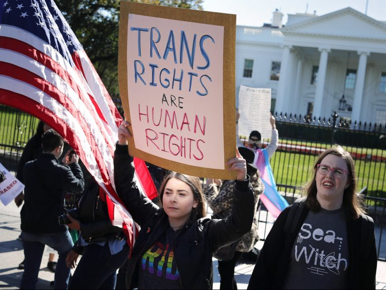 "People protesting outside of the white house with a sign that reads ""Trans Right are Human Rights"""