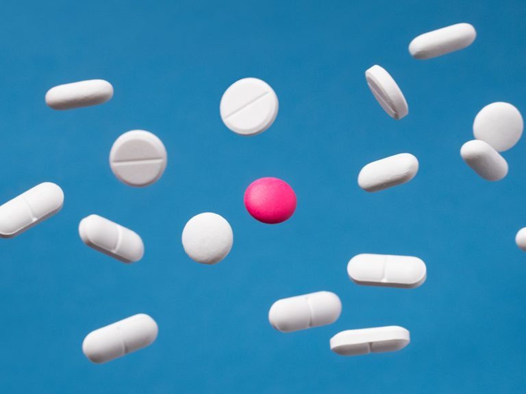 white pills on a blue background with one pink pill