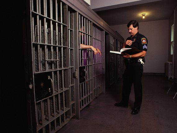 Police officer standing by a jail cell