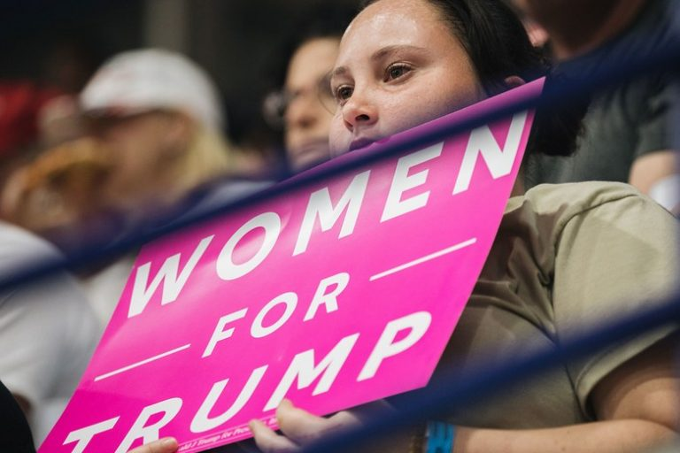 "woman holding ""women for trump"" sign"