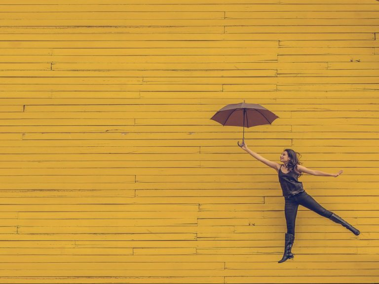 person jumping with an umbrella