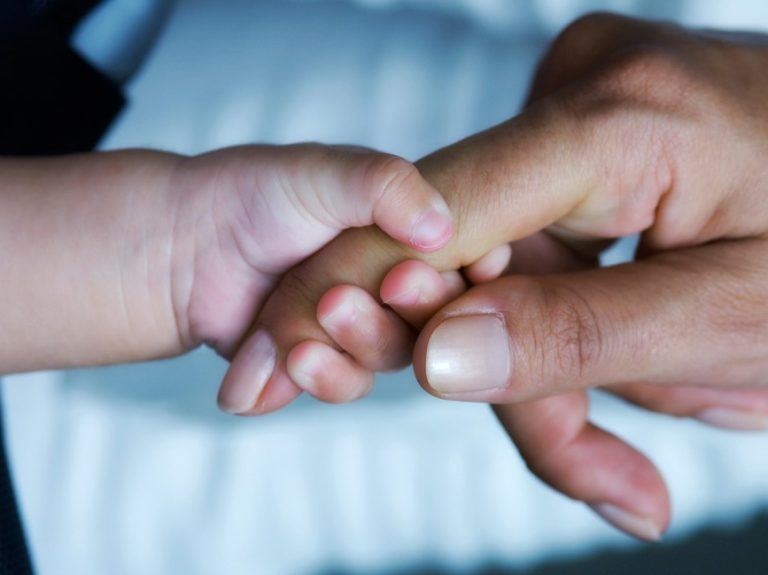 a babays hand holding on to a parents finger