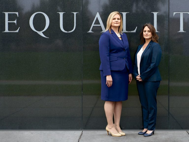 "two people stand in front of an ""equality"" sign"