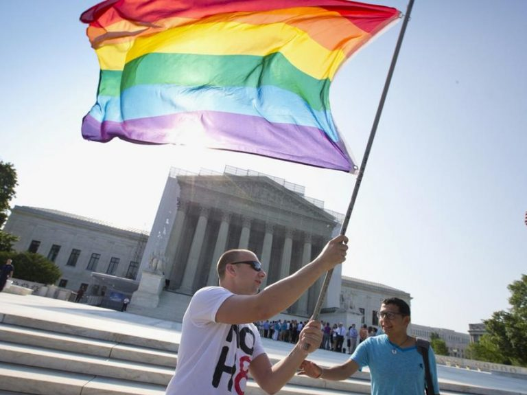 Person waves a Pride flag in front of the supreme court