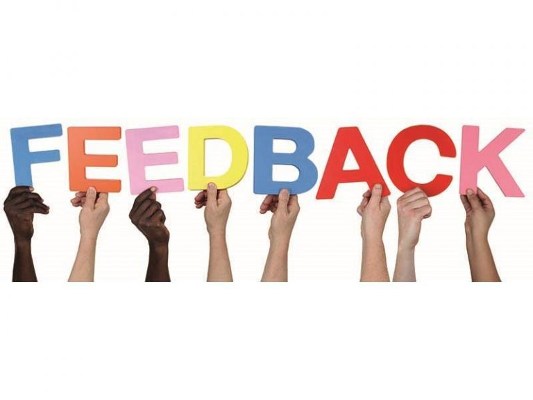 """People holding up letters that spell """"Feedback"""""""