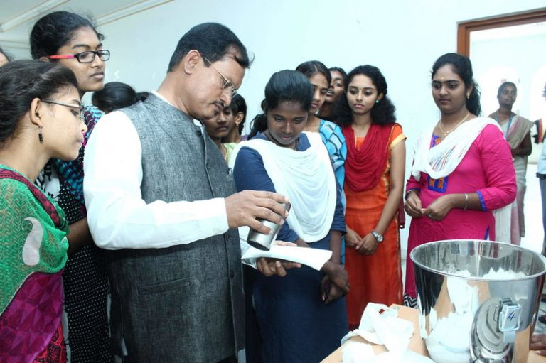 Arunachalam Muruganantham, inventor of a menstruation pad machine, tests the quality of the pads as local women, who are eager to learn how the machine works, look on