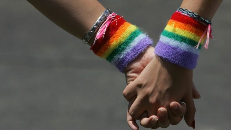 two people holding hands with LGBTQ flag wristbands