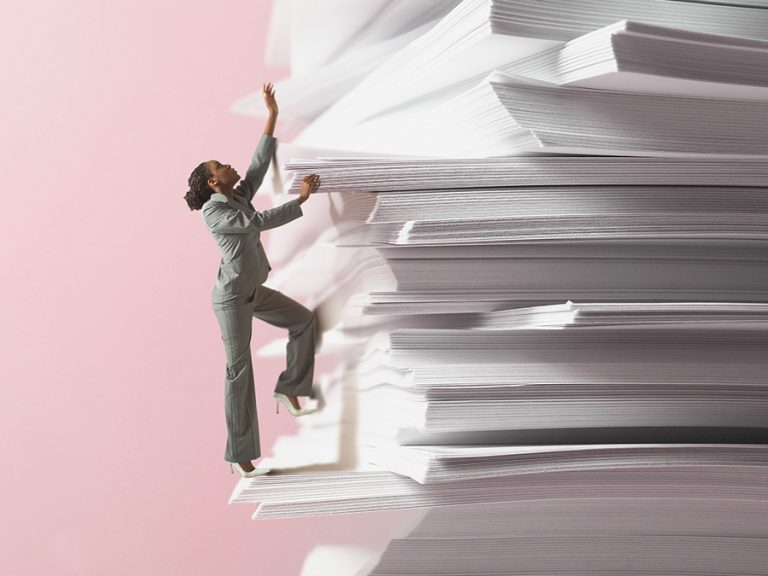 woman climbing a stack of papers