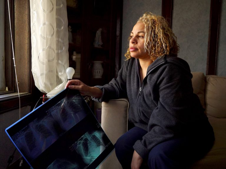 Eugenia Colon holding an X-ray of her lungs from 2010. In the nail salon she owned in Brooklyn, she molded talon-like nails in a haze of acrylic powder, ignoring a persistent cough