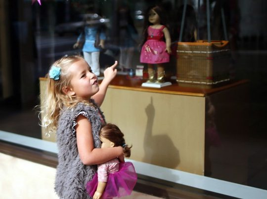 Charli Crosby, 5, points to a doll in the window of an American Girl store at The Grove mall in Los Angeles November 26, 2013. This year, Black Friday starts earlier than ever, with some retailers opening early on Thanksgiving evening. About 140 million people were expected to shop over the four-day weekend, according to the National Retail Federation. REUTERS/Lucy Nicholson (UNITED STATES - Tags: BUSINESS) - RTX15UG2
