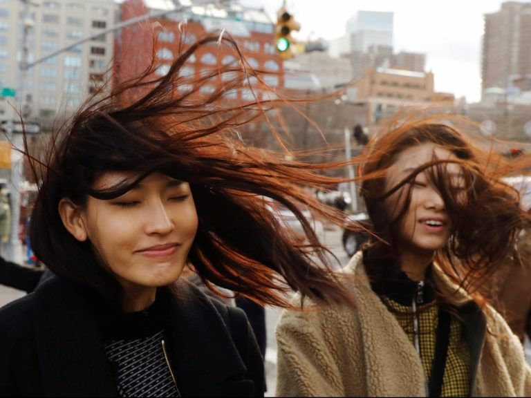 two women with wind blowing their hair