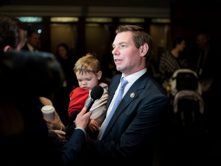 Representative Eric Swalwell talking to reporters while holding his son Nelson after a House Democratic Caucus meeting on Capitol Hill in Washington in November