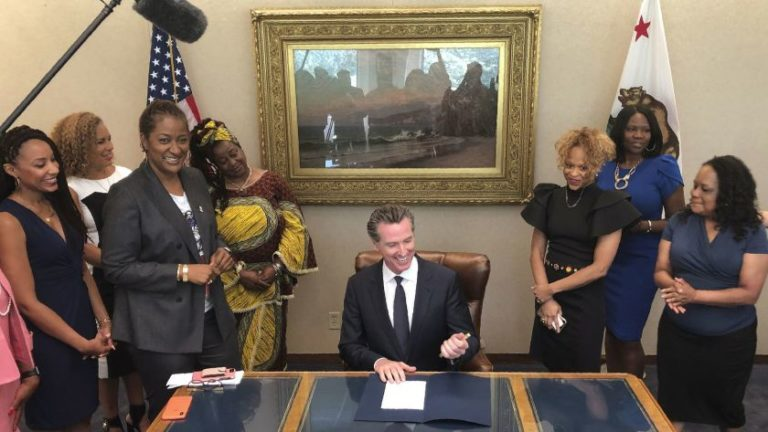 black women standing around a table as governor signs bll