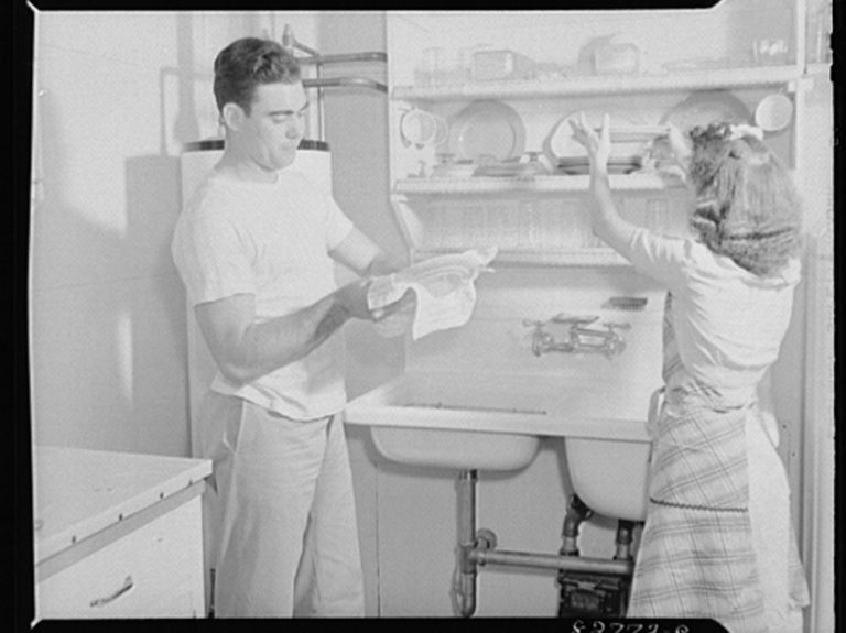 """The Smiths share the drudgery of housework, for they both have important war jobs,"" the Office of War Information wrote about this photo circa 1944."