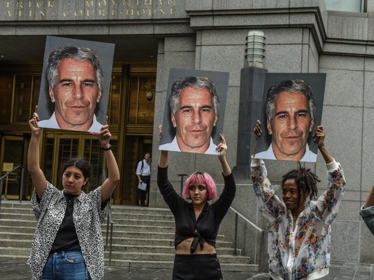 "A protest group called ""Hot Mess"" hold up signs of Jeffrey Epstein in front of the Federal courthouse on July 8, 2019 in New York City. According to reports, Epstein will be charged with one count of sex trafficking of minors and one count of conspiracy to engage in sex trafficking of minors."