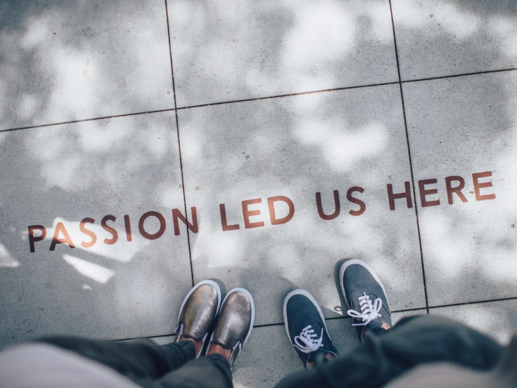 "Looking down at two people's shoes standing next to ""passion led us here"" written on the sidewalk."