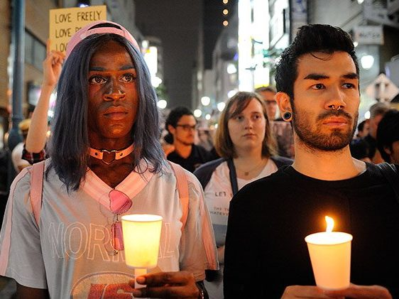 two people holding candles at a vigil