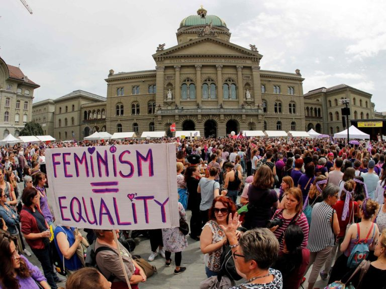 "A woman holds a sign reading ""Feminism = Equality"" as she takes part in a nation-wide women's strike for wage parity outside the federal palace, on June 14 in the Swiss capital Bern."