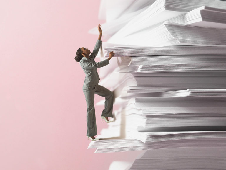 woman climbing stack of papers